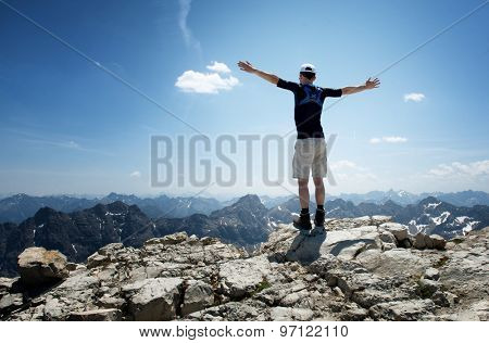Rear View of Male Hiker on Top of Mountain with his arms wide spread enjoying the wild nature and freedom. Image for climbing, trekking or hiking.