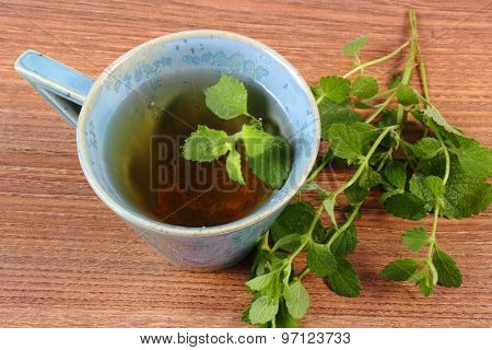 Fresh Lemon Balm And Cup Of Herbal Drink On Wooden Table