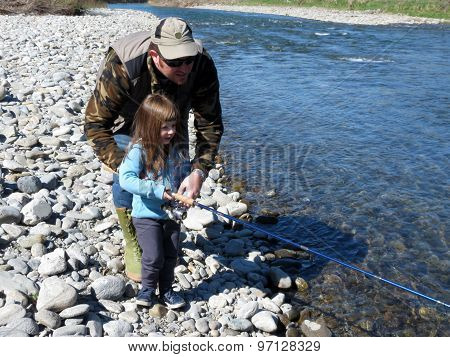 a cheerful father and daughter fishing togheter