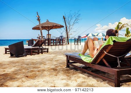 Relaxing and reading on the beach. The woman's face is not recognizable