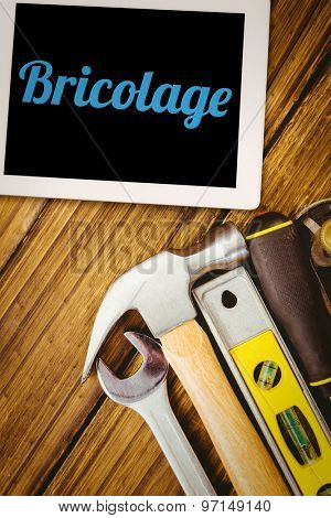 The word bricolage and tablet pc against desk with tools
