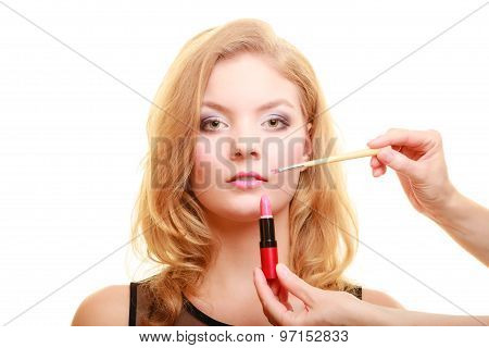 Cosmetic beauty procedures and makeover concept. Makeup artist applying lipstick with accessories tools to woman lips. Isolated studio shot poster
