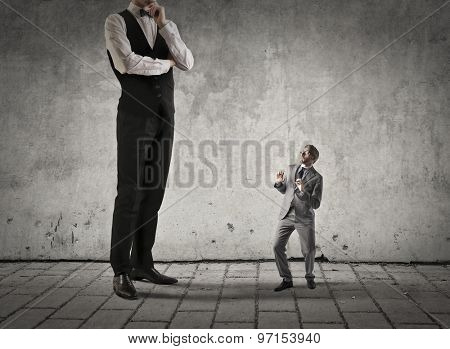 Scared employee standing in front of his boss poster