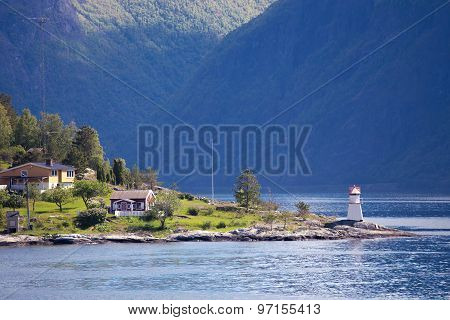 lighthouse and multicolored houses on a fjord shore poster