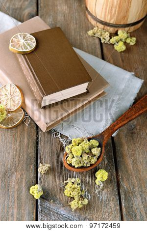 Old books with dry flowers and lemon on table close up