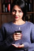 Pretty young woman with wineglass on wine shelf background poster