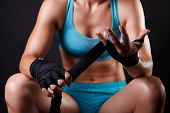 Fighter woman Putting Boxing Bandage On Her Hands poster