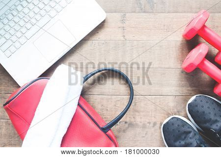 Flat lay of laptop computer and sport equipments on wood background. Workout and Healthy lifestyle top view