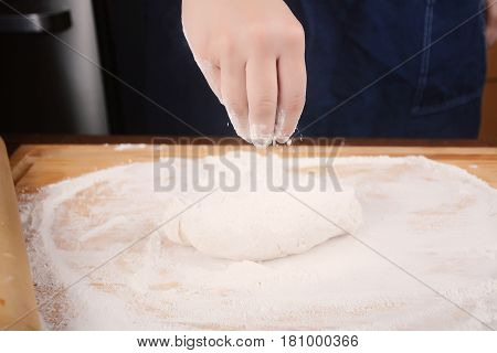 Woman Hand Adding Flour To Dough.