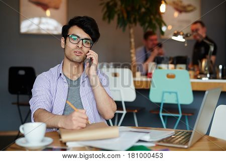Portrait of young creative man wearing casual clothes and glasses  making notes while calling by phone and working with laptop in cafe