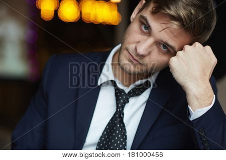 Portrait of young tired businessman wearing formal suit looking at camera with serious neutral expression resting head on hand