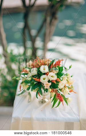 Wedding bridal bouquet of Proteus, Verdure Italian , Lisianthus on a table. Wedding in Montenegro, Adriatic.