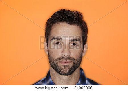 Handsome chap in in blue shirt and orange studio shot