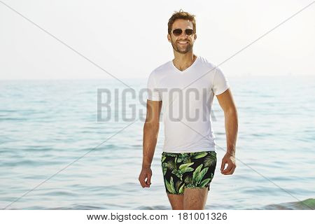 Smiling dude on beach wearing t-shirt and shorts portrait