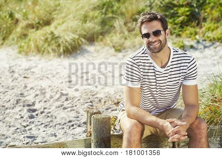 Beach guy smiling in shades and stripes portrait