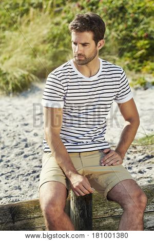 Handsome summer Dude sitting on beach in shorts