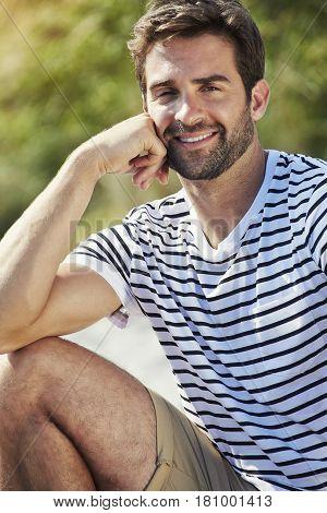 Handsome summer Holiday dude sitting on beach portrait