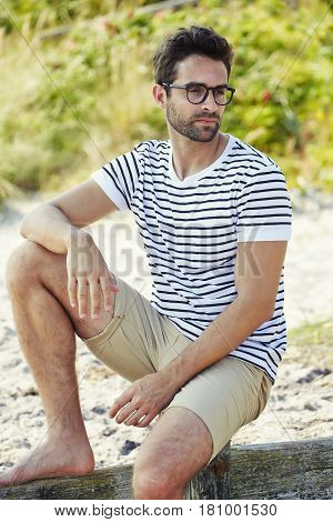 Handsome summer Shorts guy on beach looking away