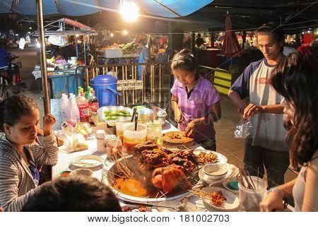 Kanchanaburi, Thailand - December 08, 2013: Food Stall with Merchant Preparing Mhoo Jum Phama (Burmese Hot Pot Pork) in Sangkhlaburi Market and Sangkhlaburi Walking Street