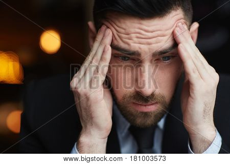 Portrait of frustrated bearded businessman rubbing his temples ooking stressed and troubled against black background