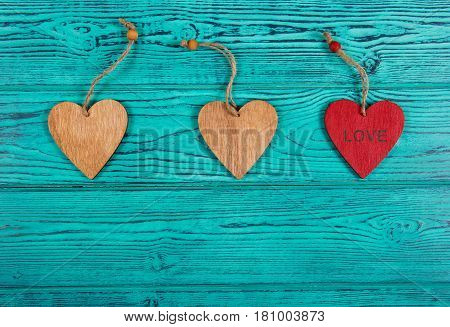 Wooden hearts on a blue background. Pendants made of wood in the form of heart. Copy space. Top view