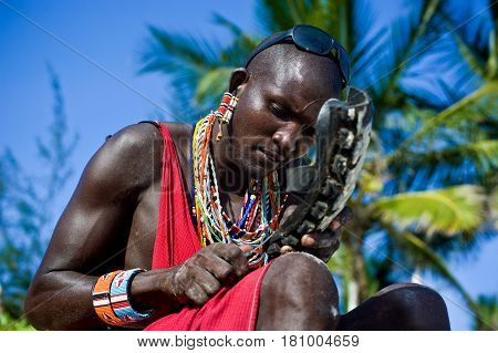 Mombasa. Kenya January 26 2012 A man of the Maasai tribe makes shoes out of an automobile tire