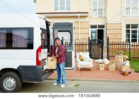 Young man unloading packed box from family van