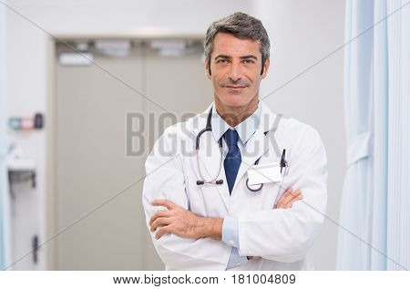 Portrait of proud doctor with stethoscope around his neck at medical clinic. Happy smiling senior doctor at hospital lobby. Mature man feeling confident after a major operation and looking at camera.