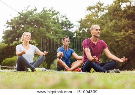 Group of middle aged people doing yoga sitting on grass. Three people practicing meditation and yoga at park on a bright morning. Mature woman and two mid men meditating together in a lotus position.