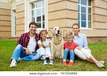 Family with pet relaxing on green grass by their new house