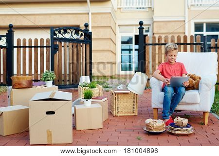 Adorable youngster with touchpad sitting in armchair with packed boxes near by