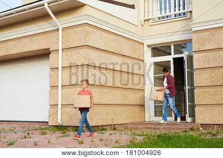 Boy with box and their father leaving cottage