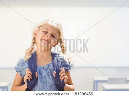 Digital composite of Young girl happy with bag in classroom