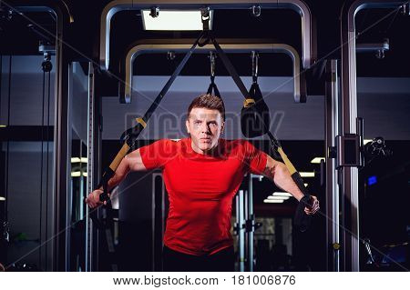 A man is doing exercises on  simulator in the gym.