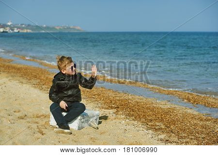 Boy with a suitcase on the beach .Young traveler and Explorer