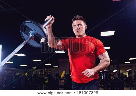 Athletic male athlete doing exercises with a barbell in the gym.