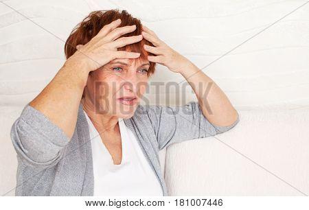 Adult woman has a headache. Sad mature female