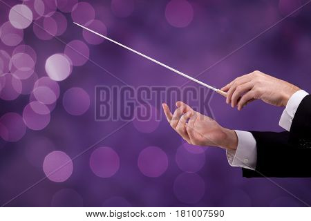 Male orchestra conductor hands with gesture, one with baton. Leadership and manager concepts.