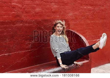 Ecstatic blond woman on red bench portrait