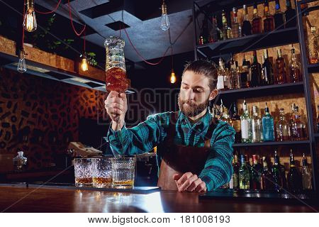 The barman pours alcohol into a glass.