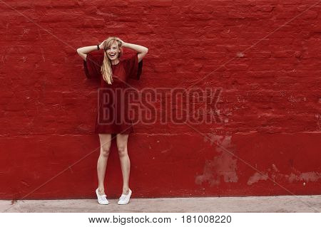 Woman in red dress against red wall portrait