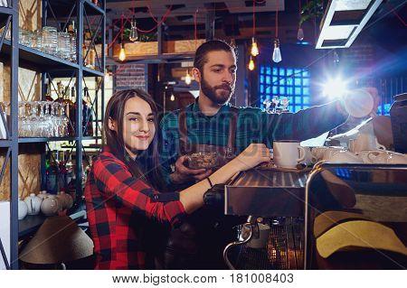 Girl waiter the barman works behind a bar rack in cafe restaurant.
