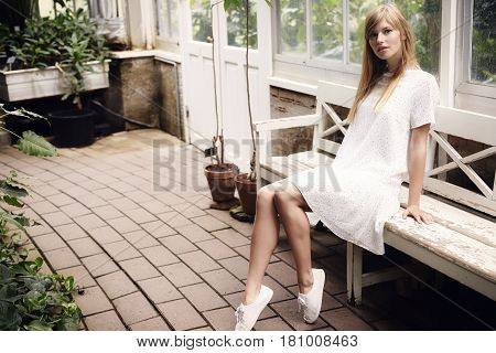 Gorgeous woman in summer dress in greenhouse portrait