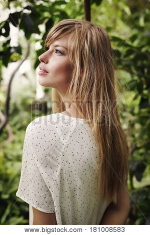 Blue eyed and blond haired woman in garden