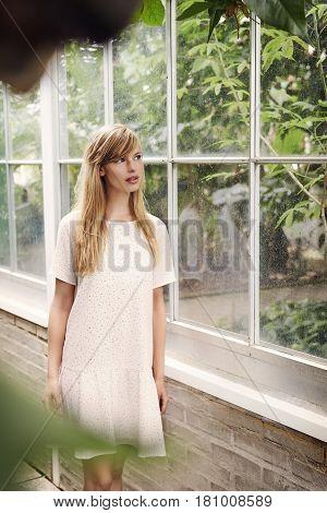 Gorgeous woman  in summer dress in garden by window
