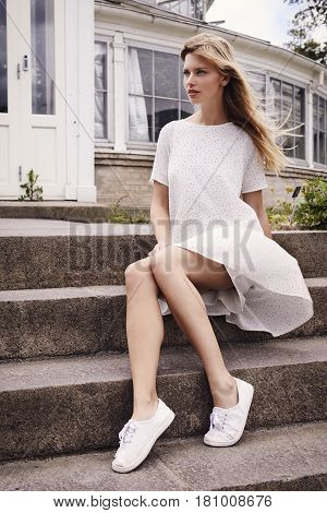 Windswept in white dress woman on steps