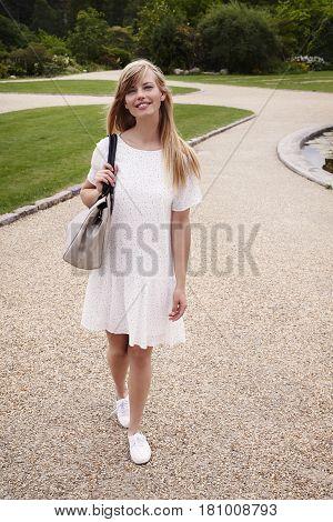 Portrait of beautiful woman in summer dress in park