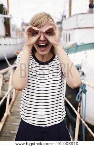 Beautiful woman with finger binoculars portrait outdoor