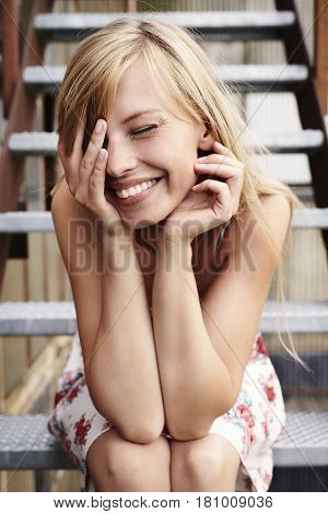 Sweet Laughing blond lady seated on steps