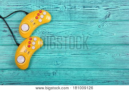 Video game console GamePad on a old blue wooden background table. Yellow retro GamePad. Copy space.